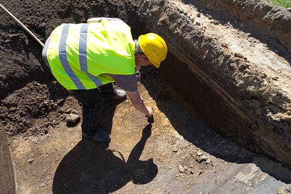 Ved de allerførste gravearbejder ved Hostrup Strand dukkede der nogle stolpehuller fra Jernalderen op. Men siden er der ikke fuldet oldtidsspor i forbindelse med kloakeringsarbejdet. På billedet arkæolog Terkel Brannet, der viser er stolpehul under Bræmbærvej. Foto: Peter Jessen