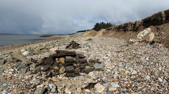 Stormene i vinteren 2011-2012 åd sig ind i skråningen langs stranden, ødelagde fiberdug og blotlagde gammelt fyld i form af bl.a. asfaltstykker. Alt blev samlet sammen og skaffet af vejen. (Foto: Peter Jessen)
