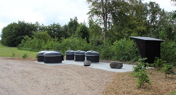 Nomi 4S har blandt andet etableret de nye affaldscontainere ved indkørslen til sommerhusområdet Vile Vestergaard i det vestlige Salling. Her står containerne i to rækker: De to store til husholdningsaffald er placeret nærmest vejen og bagved containerne til papir, glas og metal. Til højre er der bygget et lille skur med plads til en bænk. Foto: Nomi 4S